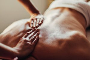 Close-up of masseur's hands and a client's back